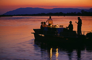 ZAM2380 Zambia, Lower Zambesi National Park. Guests enjoying sundowners on a barge on the Zambezi River.