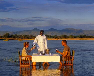 ZAM4178 Zambia, South Luangwa National Park.  A couple  on a walking safari with the Bushcamp Company enjoy a romantic bush dinner in the  Kapamba River.