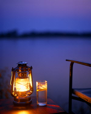 ZAM6891 Zambia, Lower Zambezi National Park, Old Mondoro Bushcamp. Gin and tonic by the light of a hurricane lamp; looking out over the Zambezi River.
