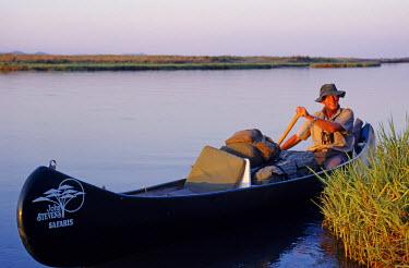 ZIM0061A John Stevens paddling his canoe on the Zambezi at sunset. Mana Pools, Zimbabwe. (MR)