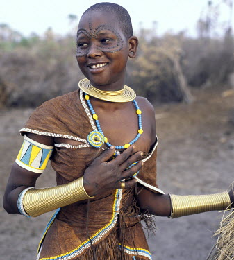 TZ2208 A Datoga woman relaxes outside her thatched house. The traditional attire of Datoga women includes beautifully tanned and decorated leather dresses and coiled brass armulets and necklaces.  Yellow and...