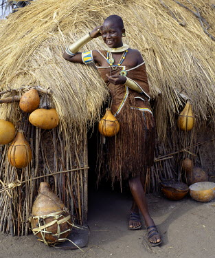 TZ2206 A Datoga woman relaxes outside her thatched house. The traditional attire of Datoga women includes beautifully tanned and decorated leather dresses and coiled brass armulets and necklaces.  Yellow and...