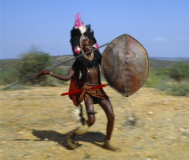 KEN4195 A Maasai warrior in full battle cry, his long-bladed spear at the ready.
