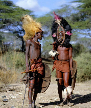 KEN4193 Two Maasai warriors in full regalia.  The headdress of the man on the left is made from the mane of a lion while the one on the right is fringed with black ostrich feathers. Their traditional weaponry...