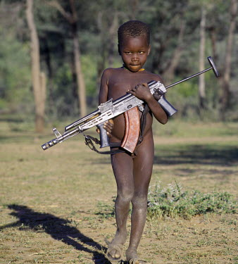 KEN4157 Modern weapons have replaced those used in traditional warfare near the troubled regions of Turkanaland, bordering Uganda and the Sudan. This young boy carries an AK47 assault rifle to his father.