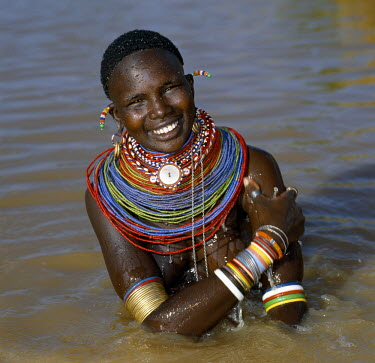 KEN4077 A Samburu woman resplendent in her beaded necklaces and numerous bracelets makes best use of a large rainwater pond to wash herself. Water is scarce in much of Samburuland.