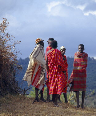 KEN4040 A group of Samburu elders confer outside a homestead while rain clouds form overhead. The status, prestige and influence of elders is determined by the number of cattle, wives and children they have....