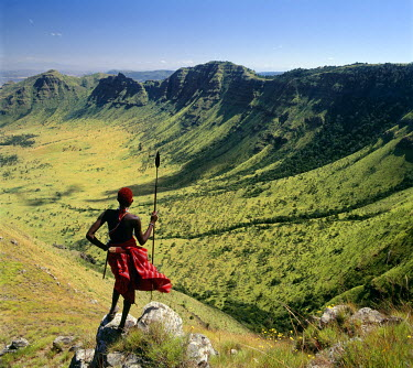 KEN4010 A Samburu warrior looks out across the eastern scarp of Africa's Great Rift Valley at Poro, Northern Kenya where the land drop precipitously 3,000 feet.
