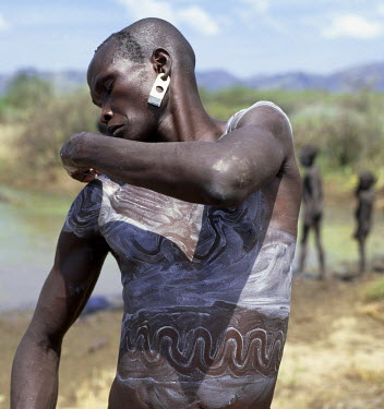 ETH1048 A Mursi man smears his body with a mixture of local chalk and water and then draws designs with his fingertips to enhance his physical appearance.The Mursi speak a Nilotic language and have affinitie...