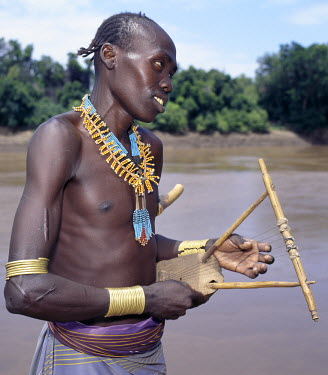 A Karo man with braided hair plays a traditional stringed instrument beside the Omo River near Duss. Young men settle disputes by fighting with hippo hide whips, which leave nasty weals on a person's...