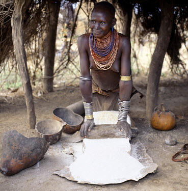 ETH1037 Shaded from the hot sun, a Karo woman grinds sorghum using large flat stones. It is customary for females of the tribe when in their teens to make a small hole in the flesh below their lower lips into...