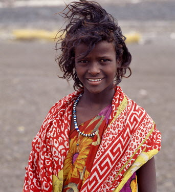 DJI1044 A pretty tousle-haired girl of the nomadic Afar tribe wears bright colours in stark contrast to the drab, windswept surroundings of Lake Abbe.