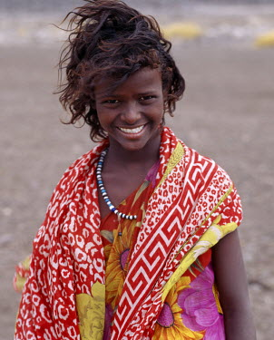 DJI1043 A pretty tousle-haired girl of the nomadic Afar tribe wears bright colours in stark contrast to the drab, windswept surroundings of Lake Abbe.