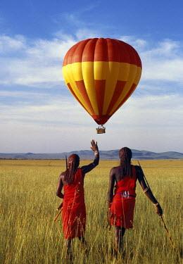 KEN4299 Two Maasai warriors watch a hot air balloon flight over Masai Mara.