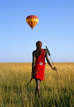 KEN4418 A Maasai Warrior watches a hot air balloon float over the Mara plains.