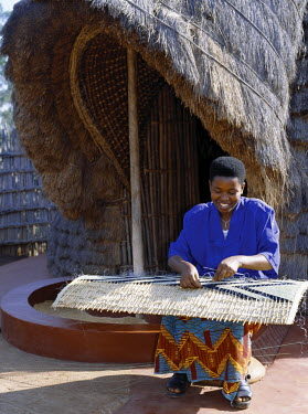 RW1065 A Rwandan girl makes a finely decorated screen to partition the interior of a traditional thatched house.  The screens are made of split cane onto which an assortment of local, long-stemmed grasses ar...