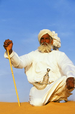 OMA1173 A Bedouin man kneels on top of a sand dune in the desert .  He wears the traditional Omani long white cloak or dish dash, a turban,  a ceremonial curved dagger (khanjar) and holds a short camel stick