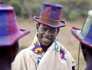 ETH1201 Konso men wear stylish, brightly-coloured hats, which they weave from locally-grown cotton.  Only men work the wooden looms but women flay the cloth to flatten the warp and weft.  Much of their produc...