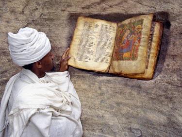 ETH1068 A Priest of the Ethiopian Orthodox Church reads a very old, beautifully illustrated bible beside the entrance to the rock-hewn church of Yohannes Maequddi. The bible's script is Ge'ez, the liturgical...
