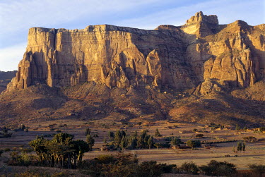 ETH1064 In the golden light of early morning, the spectacular Gheralta Mountains of Northern Ethiopia dwarf Tigray homesteads built on the Hawzien Plain hundreds of feet below.  Flat-roofed stone houses, whic...