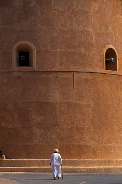 OMA1389 An old Omani man walks beneath the imposing watchtower of Al Hazm Castle.  The magnificent 18th century military stronghold makes full use of traditonal Omani defensive features boasting a massive woo...