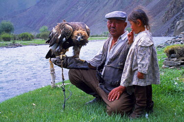 MON1131 Mongolia, Khovd (also spelt Hovd) aimag (region), Kasakh hunter with eagle by the Khovd River, with a small child. Eagles are trained by the Kasakh people of Western Mongolia and used in hunting foxes...