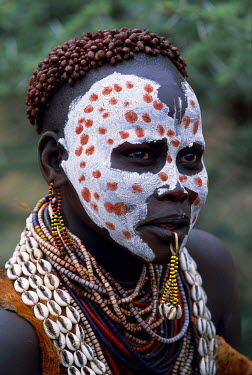 ETH1386 A Karo woman shows off her attractive face paint, layers of necklaces and hairdo styled with mud and ochre.  A small Omotic tribe related to the Hamar, who live along the banks of the Omo River in sou...