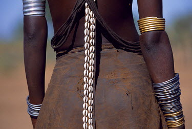 A young Dassanech girl wears a leather skirt, metal bracelets and amulets and layers of bead necklaces. A long leather strap decorated with cowrie shells hangs down her back. Much the largest of the...