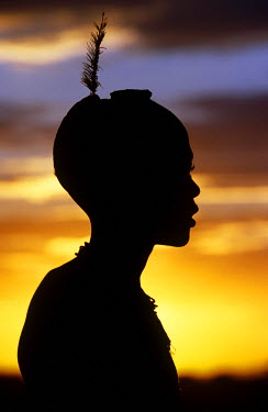 ETH1864 Ethiopia, Omo Valley.  A young Dassanech boy silhouetted against the evening sky at his village.