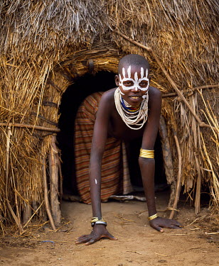 ETH1962 A young Karo girl in the doorway of her hut in the village of Duss.  A small Omotic tribe related to the Hamar, who live along the banks of the Omo River in southwestern Ethiopia, the Karo are renowne...