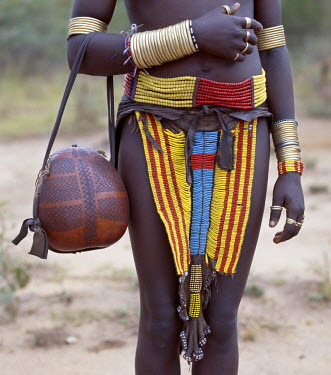 A close-up of a beautifully decorated leather apron and other adornments worn by a Bena girl. Her handbag is a finely decorated gourd.The Bena are a small tribe living in remote Southwest Ethiopia.