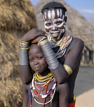Two pretty Karo girls in traditional attire. Most girls pierce a hole below the lower lip in which they place a thin piece of metal or a nail for decoration. They will paint their faces with local wh...