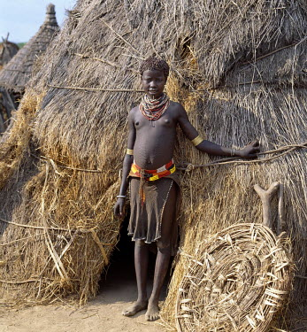 A Karo girl in traditional attire stands outside her family's home. The 'door' of the low entrance to the house is propped against its thatched wall. Most girls pierce a hole below the lower lip in wh...