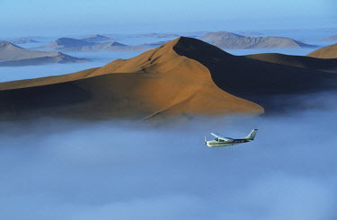 Safari flights over red sand dunes of Sossusvlei with early morning mist, Namib-Naukluft National Park, Namibia.