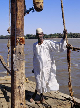 SUD1128 A Nubian boatman on his felucca, a wooden sailing boat that plies the waters of the River Nile in Egypt and The Sudan.