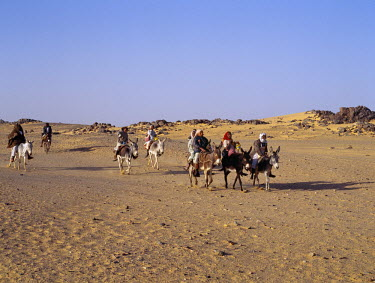 SUD1126 Children ride to school on donkeys along the edge of the Northern or Libyan Desert in northwest Sudan.