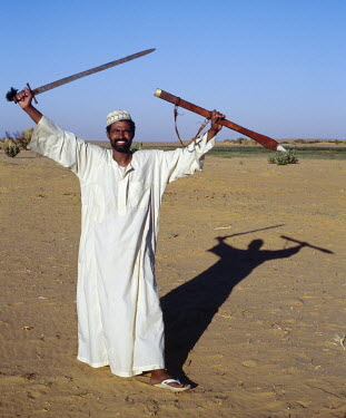 SUD1137 A Nubian man displays his sword at an oasis in the Nubian Desert north of Old Dongola.
