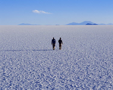 BOL8219 Two tourists walk across the endless salt crust  of the Salar de Uyuni, the largest salt flat in the world at over 12,000  square kilometres.