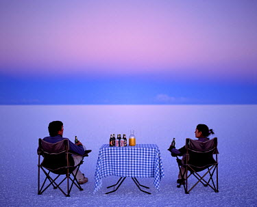 BOL8226 Tourists enjoy sundowners while looking out across the endless salt crust  of the Salar de Uyuni, the largest salt flat in the world at over 12,000  square kilometres.