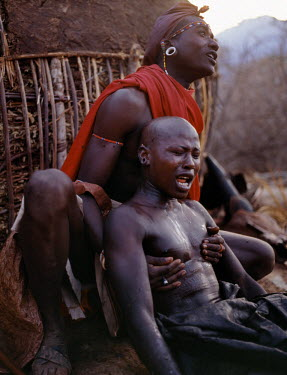 KEN5165 Early in the morning, a Samburu youth sings the lebarta, the Samburu circumcision song, just after he has been circumcised outside his mother's house. One of his sponsors attends him by holding his ba...