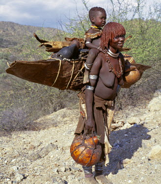 ETH2049 A Hamar mother and child moving home. The mother carries all her possessions with her including sleeping mats and gourds.The Hamar of Southwest Ethiopia are semi-nomadic pastoralists whose whole way...
