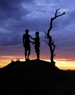 ETH2053 Two Hamar children silhouetted by the setting sun. The Hamar of Southwest Ethiopia are semi-nomadic pastoralists whose whole way of life is based on the needs of their stock. They live in the Hamar M...