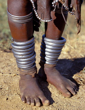 ETH2055 The heavy metal ankle ornaments of a Hamar woman of Southwest Ethiopia. The Hamar are semi-nomadic pastoralists whose richly-ochred women have striking styles of traditional dress.  Skins are widely...