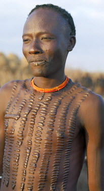 ETH2137 The extensive scarification of this Dassanech man means that he has killed an enemy in battle. The cicatrix are raised by rubbing ash into them immediately after the incisions have been made.The Omo...