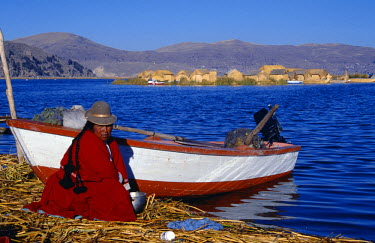 PER2917 An Indian woman from the Uros or floating reed islands of Lake Titicaca, washes her pans in the water of the lake