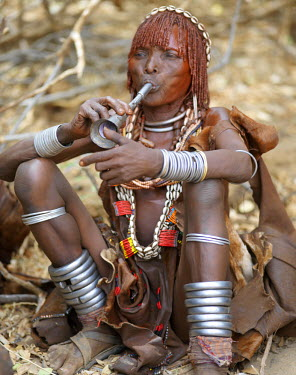 ETH2235 A Hamar woman blows a tin trumpet at a 'Jumping of the Bull' ceremony. The Hamar are semi-nomadic pastoralists of Southwest Ethiopia whose women wear striking traditional dress and style their red-oc...