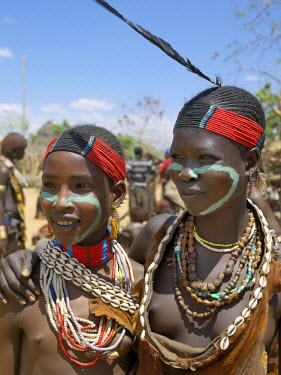 ETH2286 Two Hamar girl in fashionable dress at Turmi market.  The Hamar are semi-nomadic pastoralists of Southwest Ethiopia whose women and girls wear striking traditional dress. Skins are widely used for cl...