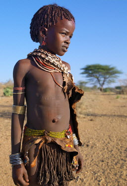 ETH2285 A Hamar girl in traditional attire.  Her leather skirt is made from the twisted strands of goatskin.  Cowries are always popular to embellish a woman's or girl's appearance.The Hamar are semi-nomadic...