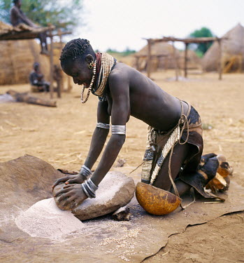 A Nyag'atom woman grinds sorghum using a flat stone. The Nyag'atom are one of the largest tribes and arguably the most warlike people living along the Omo River in Southwest Ethiopia. They form a pa...