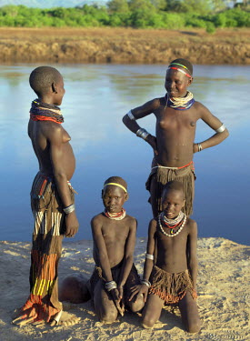 ETH2338 A group of Nyag'atom girls with braided leather aprons and beautifully decorated supple goatskin skirts relax on the banks of the Omo River.The Nyag'atom are one of the largest tribes and arguably th...